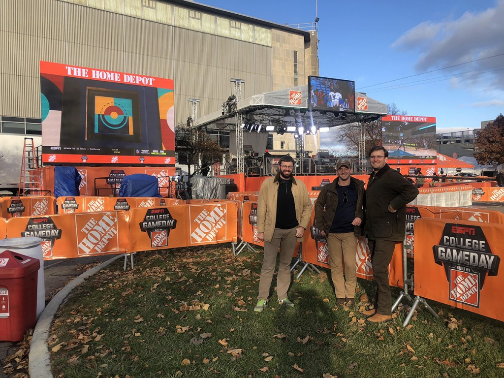 Christopher, Zachary, and Michael in front of the GameDay set as the crew sets up