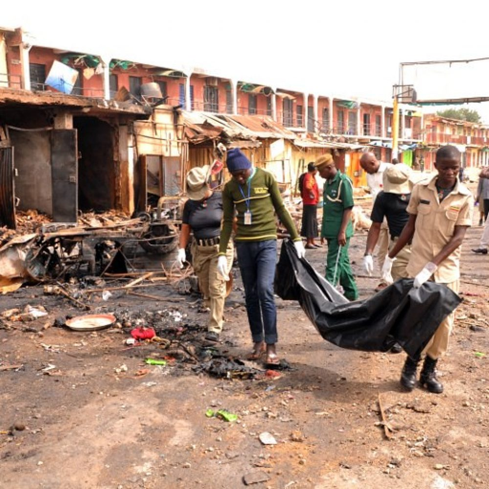 Rescuers carry a body recovered from a burnt shop at the scene of twin bomb blasts at terminus market  in the central city of Jos on May 21, 2014.  Twin car bombings in central Nigeria killed at least 118 people and brought entire buildings down Tuesday, in the latest affront to the government's internationally-backed security crackdown. Nigerian President Goodluck Jonathan swiftly condemned the attack in the central city of Jos, calling it a